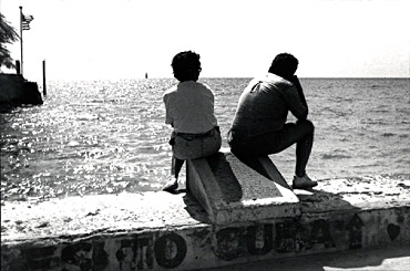 Exilio by Jose A. Figueroa -- cuba -- A Cuban couple, sitting on the southernmost point of the United States in Key West, looking southward, 95 miles, to their beloved Cuba.